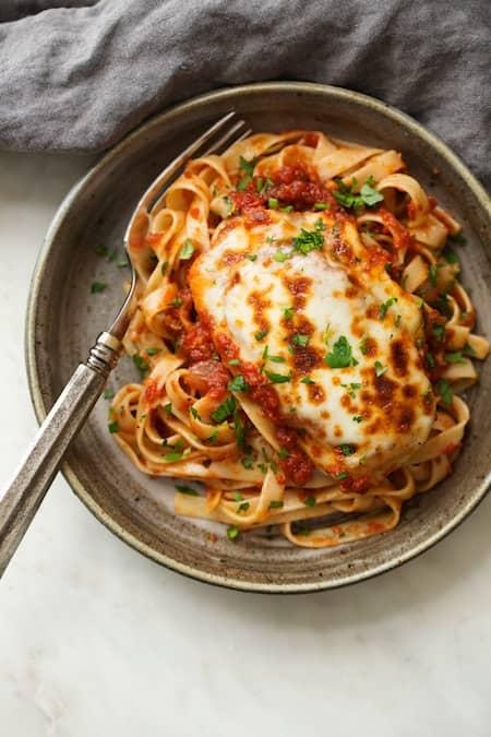 une assiette de poulet mozzarella sauce tomates servies avec des pâtes