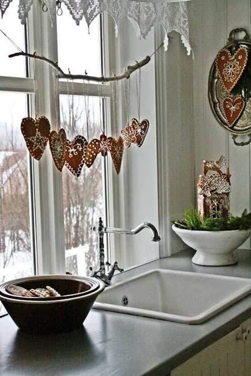 Une guirlande en bois accrochée sur la fenêtre de la cuisine avec des coeurs rouge