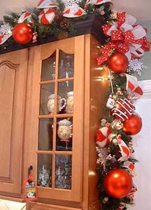 Guirlandes boules rouge et ruban blanc accrochés au placard de la cuisine