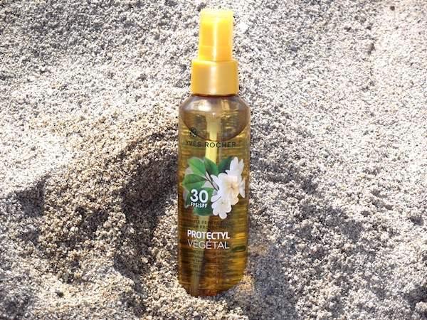 un flacon d'huile solaire en spray Yves Rocher dans le sable
