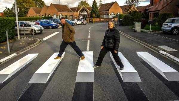 des piétons traversent sur un passage peint en 3 D en France