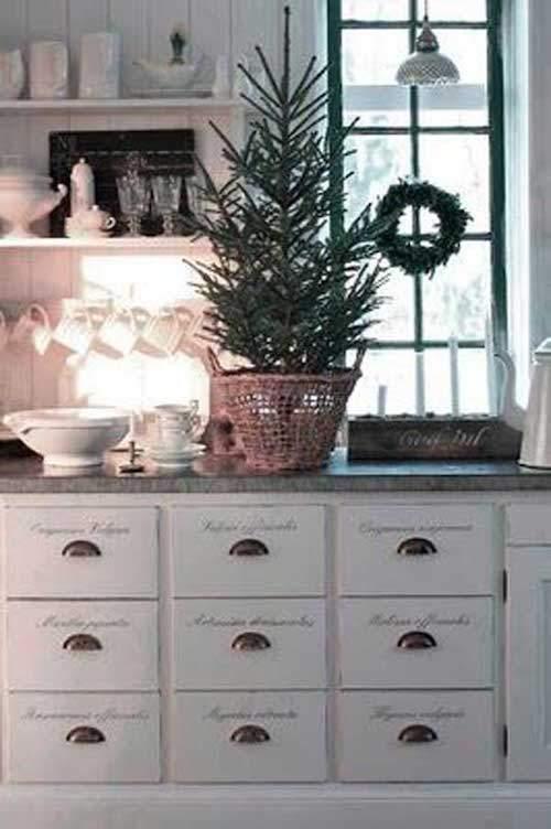 Petit arbre de Noël dans un panier posé sur le plan de travail de la cuisine