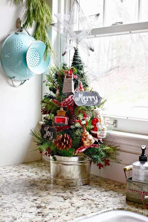 Un petit arbre de noel décoré et planté dans un pot devant la fenêtre de la cuisine