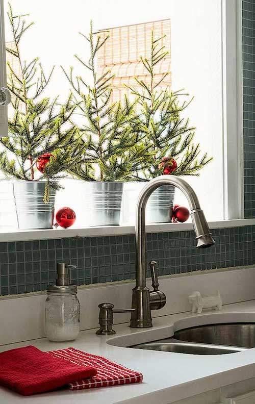 3 petits arbres de Noël sur le rebord de fenêtre de la cuisine