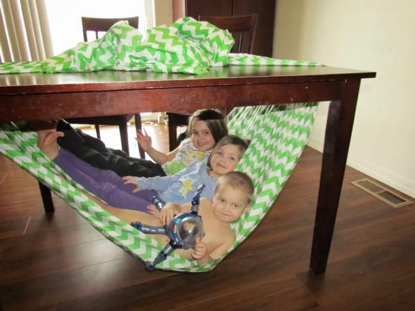 un hamac pour les enfants fait avec un drap accroché sous une table