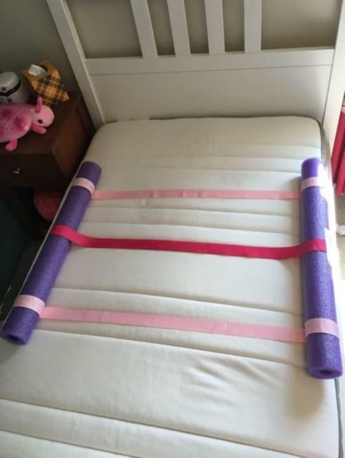 des nouilles de piscine pour sécuriser un lit