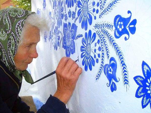une grand-mère tchèque peint des fleurs sur les murs des maisons