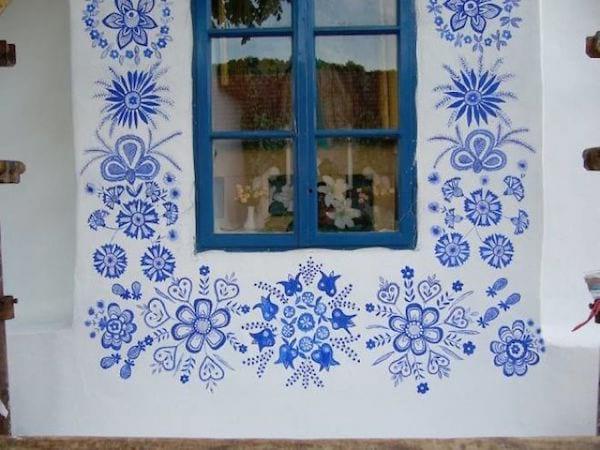 un mur est décoré avec des fleurs peintes en bleu autour d'une fenêtre
