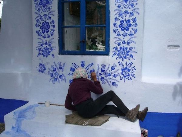 Allongée par terre, la grand-mère peint des motifs traditionnels sur les murs des maisons