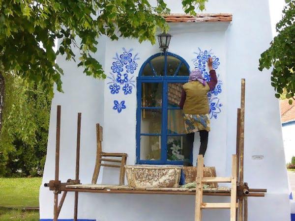 Debout sur un échafaudage, une grand-mère de 90 ans peint les murs des maisons