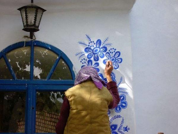 Une vieille habitante de Londa en Tchéquie décore une maison de motifs traditionnels