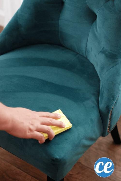 Une main qui enlève une tache de marqueur indélébile sur un fauteuil en micorfibre.