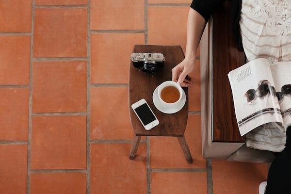 une femme lit un magazine dans son canapé tout en prenant un thé