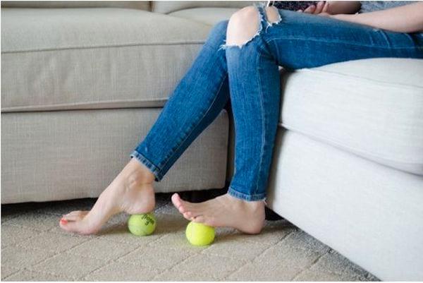 Pour soulager les pieds fatigués, faites rouler les balles de tennis sous les pieds