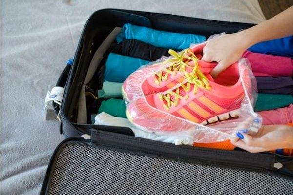 Un bonnet de douche isole les chaussures sales dans la valise