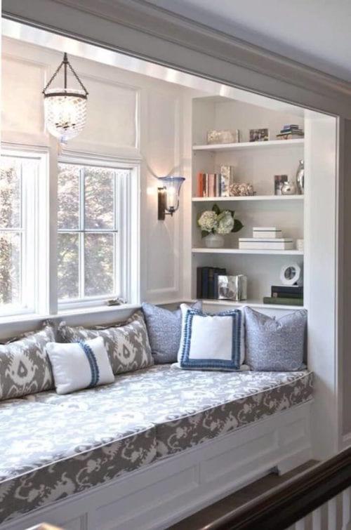 une banquette est mise sous une fenêtre avec une étagère pour faire un espace détente