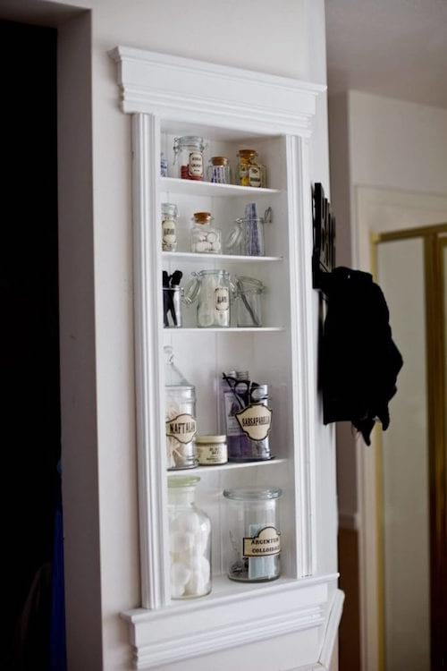 une étagère dans un mur de la salle de bains décorée de moulures