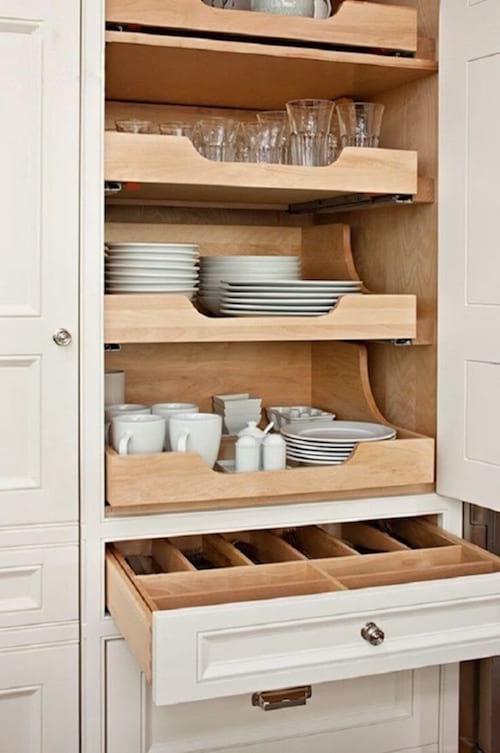 des étagères télescopiques en bois dans un placard pour ranger toute la vaisselle dans la cuisine