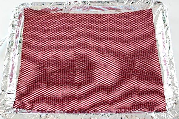 Carré de tissu posé sur une feuille de papier d'alu sur une plage à pâtisserie