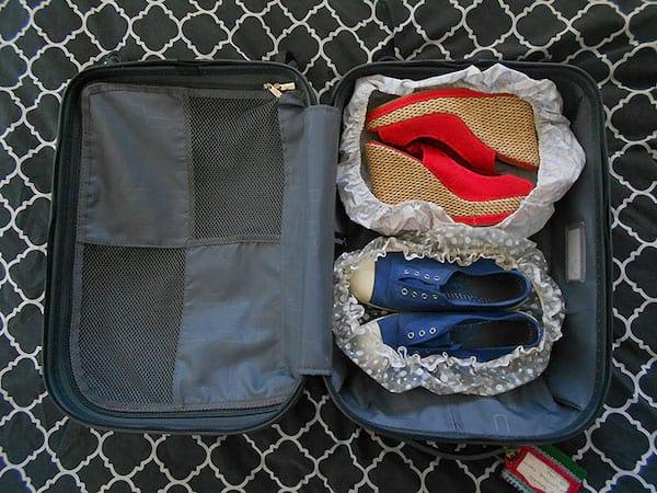 Les chaussures sont rangés dans la valise dans des bonnets de bain