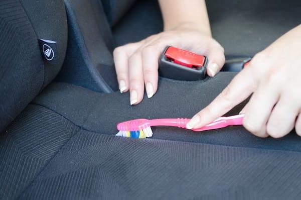 Nettotage entre les coutures du siège avec une vieille brosse à dents