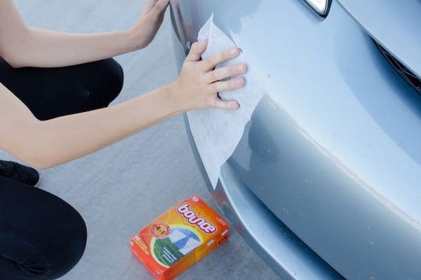 Nettoyer le pare-chocs de la voiture avec un voile de sèche-linge