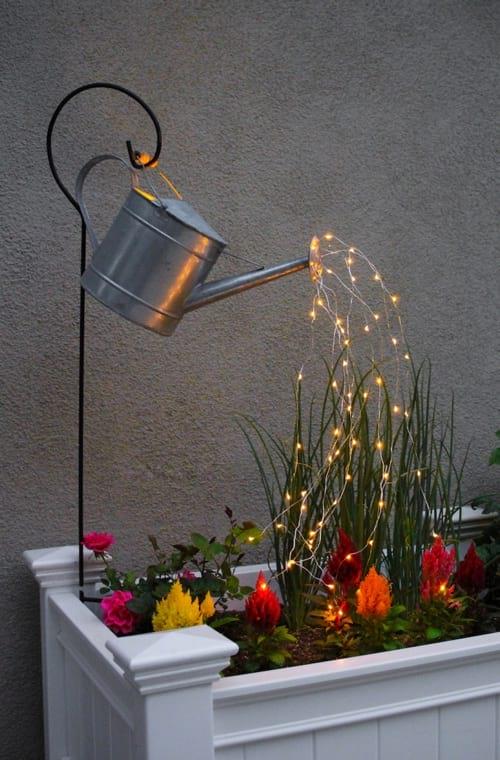 un arrosoir avec une guirlande lumineuse pour décoration dans le jardin