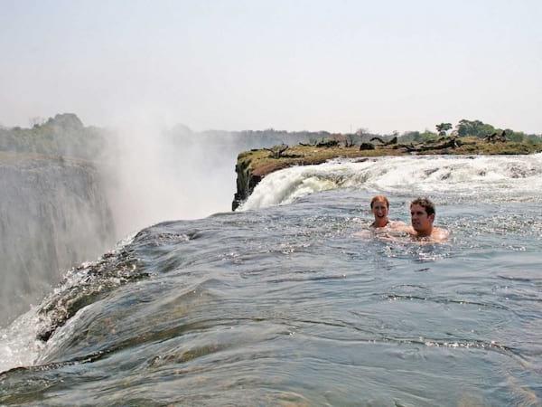 2 personnes qui se baignent dans la piscine du diable au bord des chutes d'eau