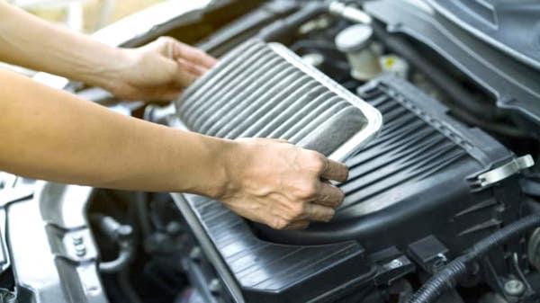 Des mains qui changent un filtre à air pour consommer moins d'essence.