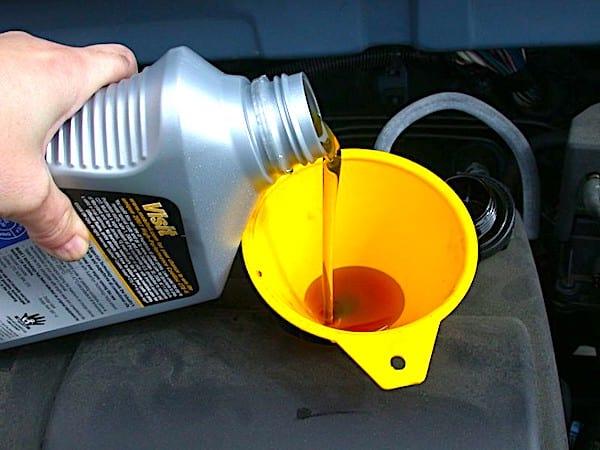 Une main qui verse le bon type d'huile dans un moteur.