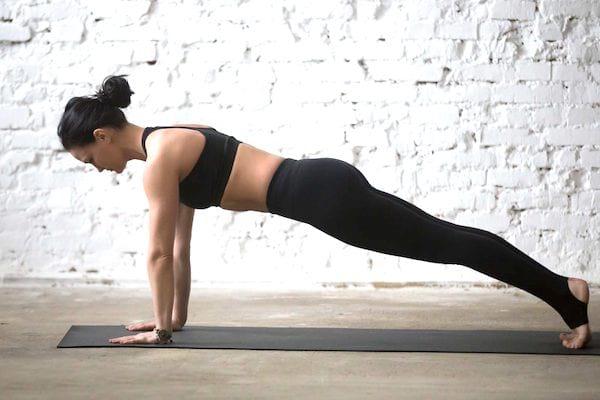 femme en legging noir qui fait la planche