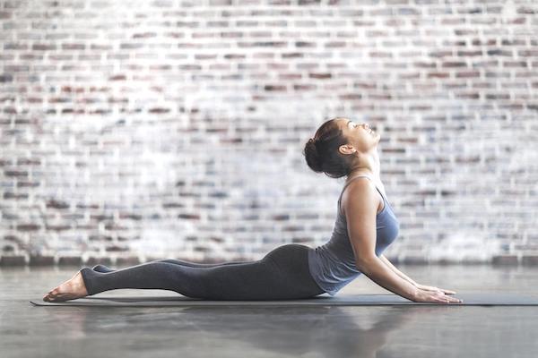 femme qui fait du yoga en legging gris et le dos en arrière