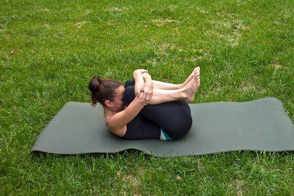 posture de yoga libération des vents avec une femme en collant noir sur l'herbe