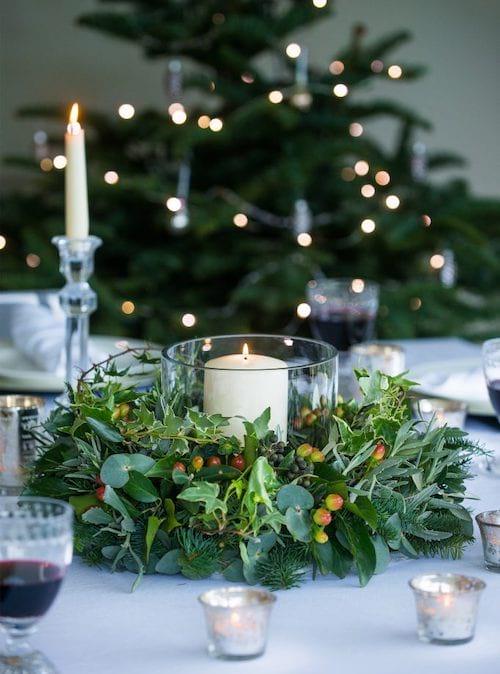 Bougies entourée d'une couronne de plantes sur table