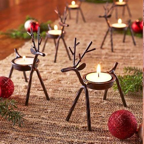 Minis rennes lumineuses sur table avec des bougies