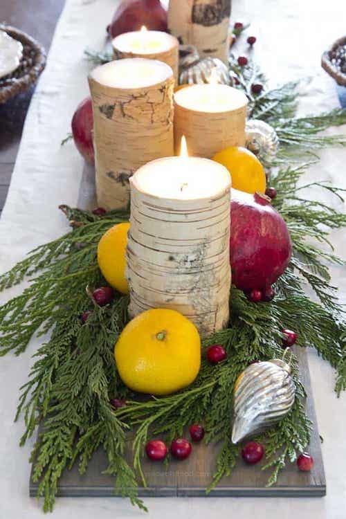 Table avec plusieurs citrons et pomme ainsi que des bougies