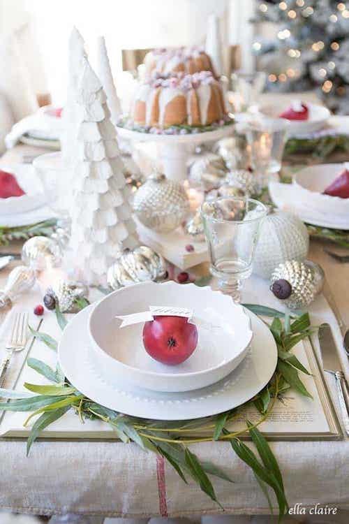Table toute blanche décorée avec une pomme rouge dans une assiette