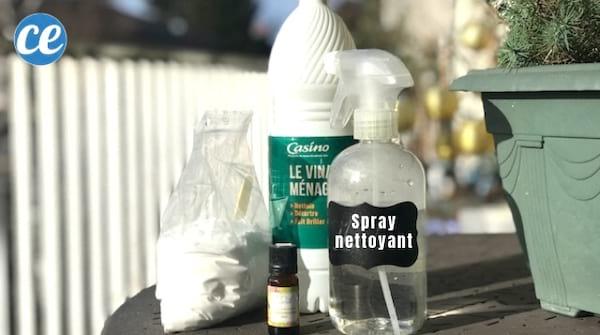 paquet de bicarbonate, bouteille de vinaigre blanc et flacon spray sur une table de jardin