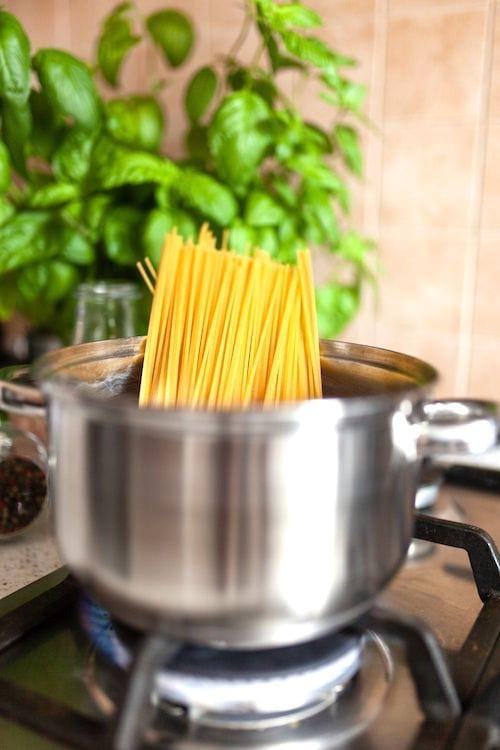 Des pâtes qui cuisent dans une casserole en métal, avec du basilic en arrière-plan.
