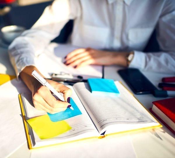 Une femme qui écrit dans son agenda.