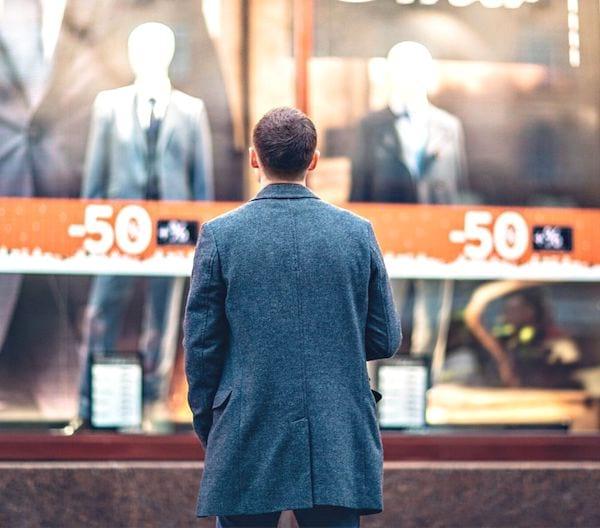 Un homme vu de dos devant une vitrine d'un magasin de vêtements.