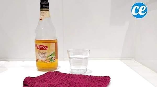 Une bouteille de vinaigre de cidre avec un verre d'eau et un gant pour faire un déodorant maison