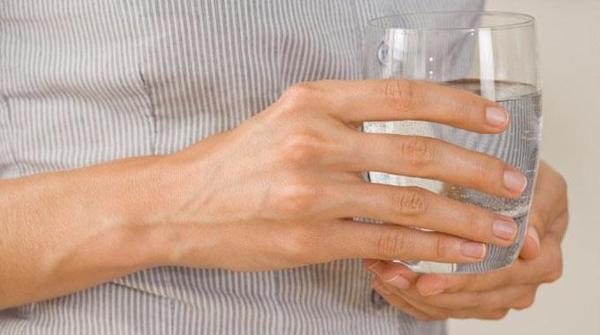 Una persona tiene un bicchiere pieno di una miscela di acqua e cloruro di magnesio