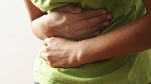 La donna tiene lo stomaco a causa del dolore causato dalla stitichezza