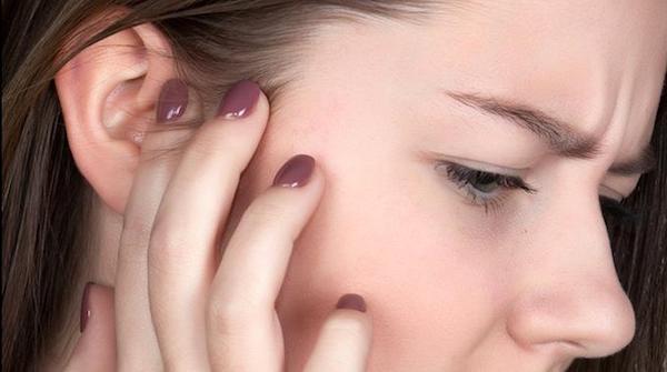 Una giovane donna si tocca l'orecchio a causa del dolore