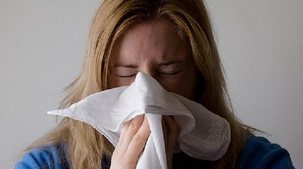 Una donna con la febbre da fieno si soffia il naso