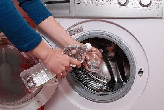 femme qui met un verre de vinaigre blanc dans la machine à laver