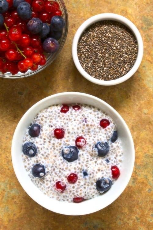 Un bol de graines de chia et un bol de fruits rouges, sur une table.