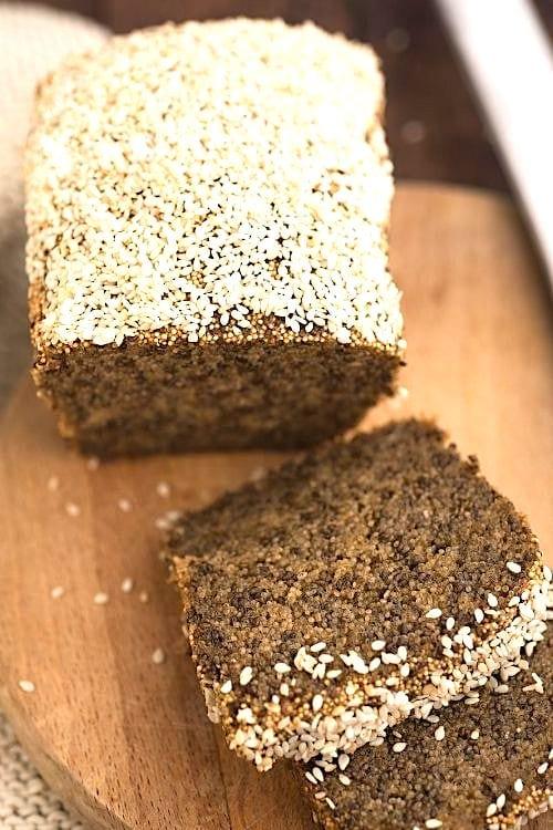 Un pain maison fait avec des graines de chia, sur une planche à découper en bois.