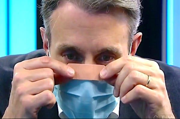 Une homme qui colle un pansement sur le masque contre la buée des lunettes